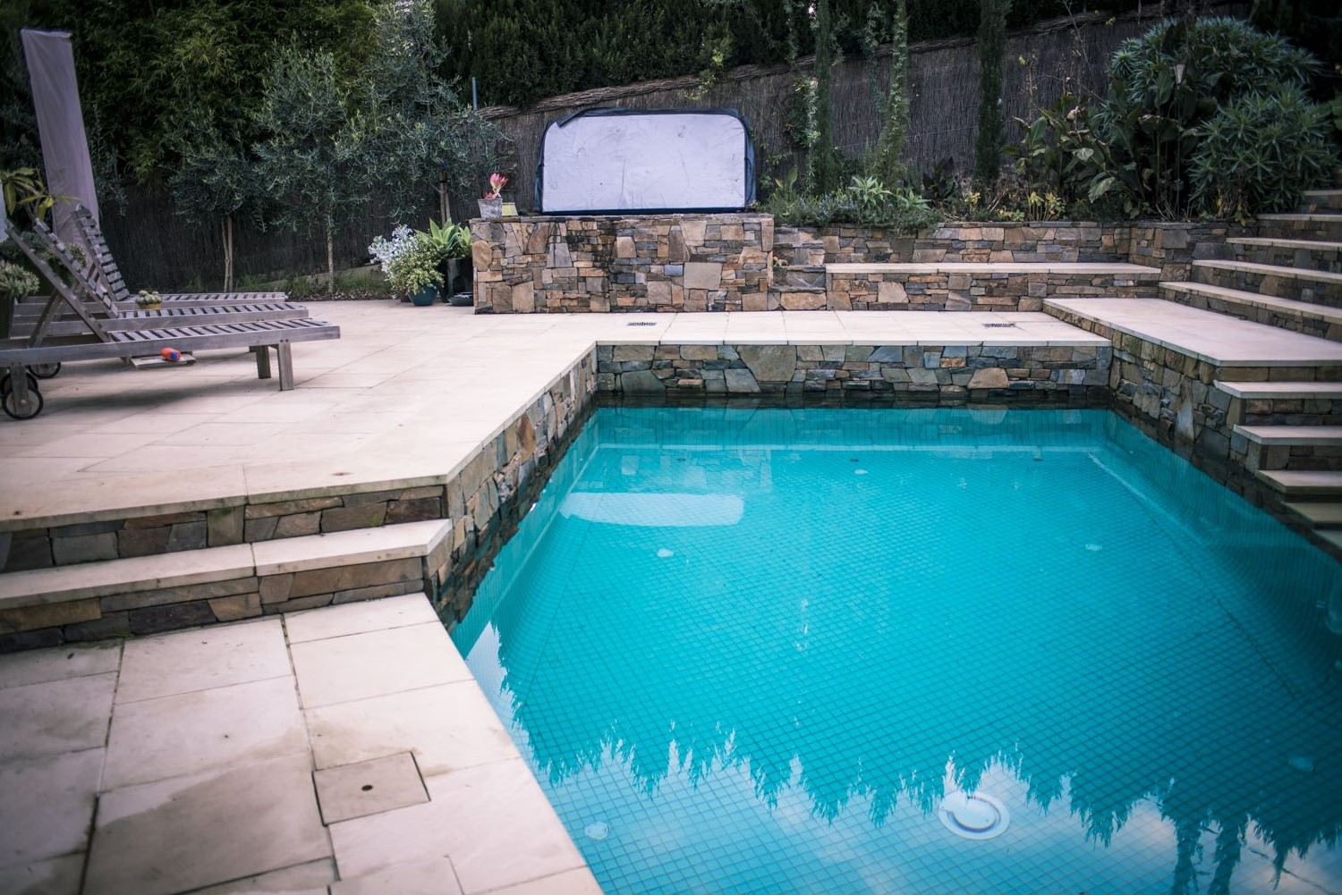 We designed this pool fit into the angled property boundaries as well as work with the sloping block. Note the way the retaining wall is continued through in the raised pool planter box that also showcases the raised spa and integrated water feature.